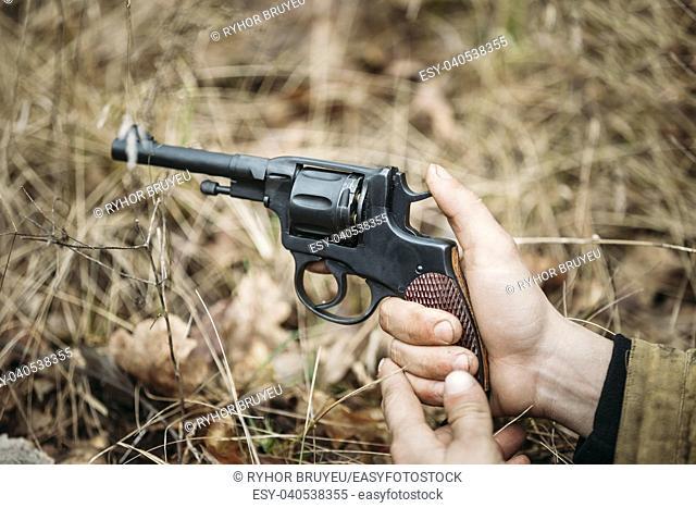 Unidentified re-enactor dressed as Soviet russian soldier holding a gun pistol World War II