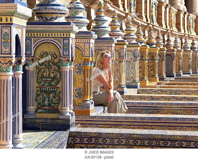 Tourist viewing ornate building in Plaza de Espana, Seville, Spain