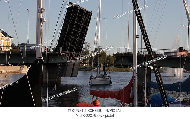 A sailing yacht steers under a lift bridge to leave a small boat harbor. Then the bridge goes down again. Härnösand, Västernorrlands Län, Sweden