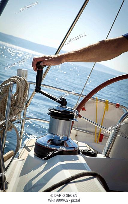 Person on sailboat working on winch, Adriatic Sea, Croatia