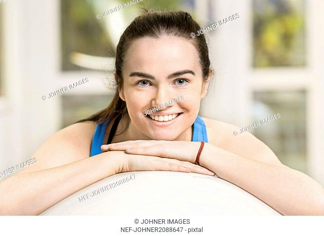 Portrait of young woman leaning against fitness ball