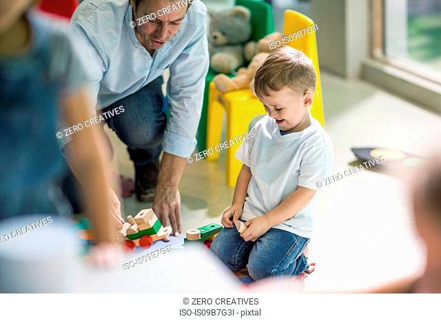 Teacher and boy playing with toy train