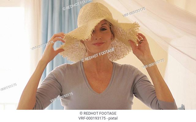 Woman in bedroom putting on hat