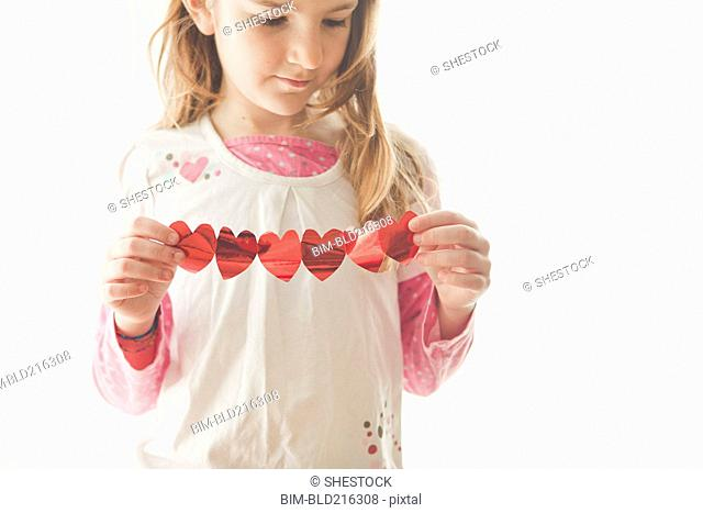Caucasian girl holding heart-shaped bunting