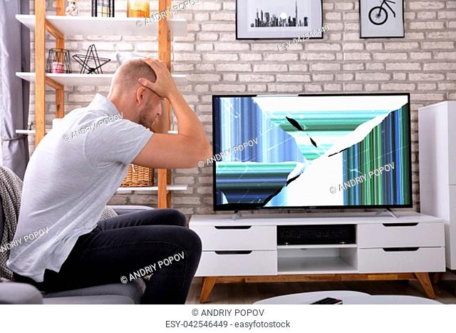 Frustrated Young Man Sitting On Sofa Near Broken TV Screen