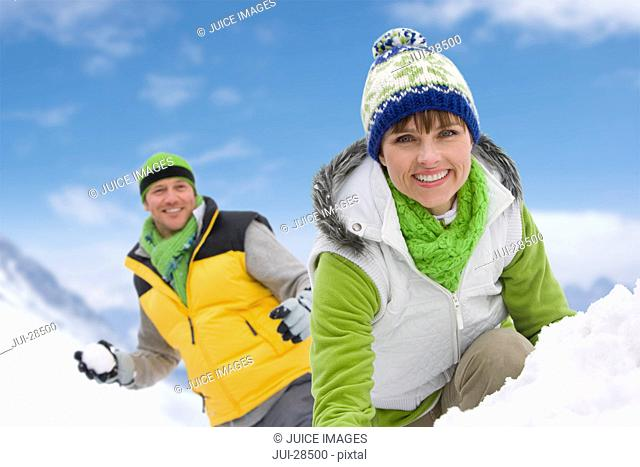 Smiling couple having snowball fight in snow together