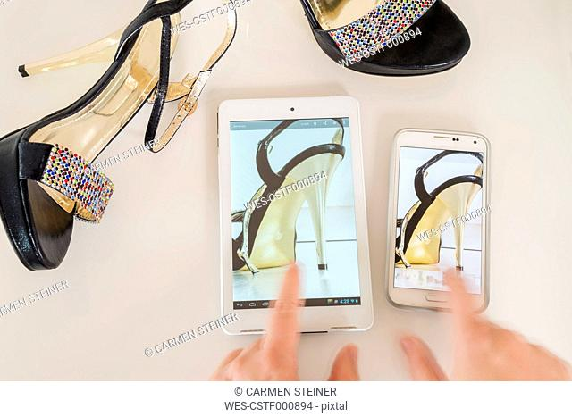 Woman using mini tablet and smartphone for comparing different offers of high heels