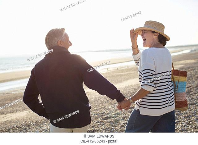 Laughing mature couple holding hands and walking on sunny beach