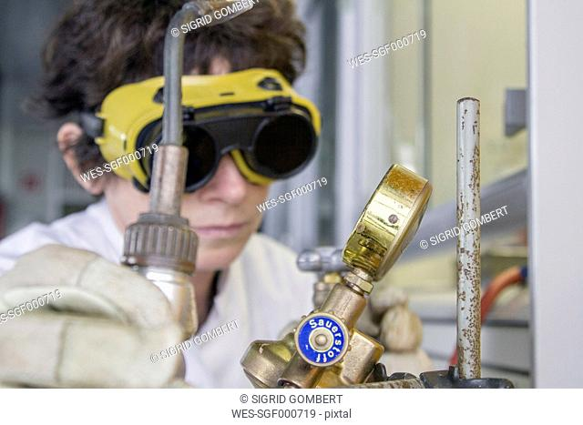 Female chemist with safety glasses and air tank in laboratory