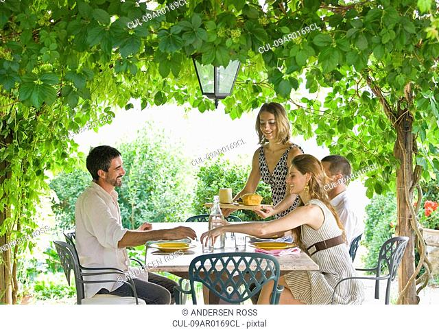 Group enjoying meal in garden