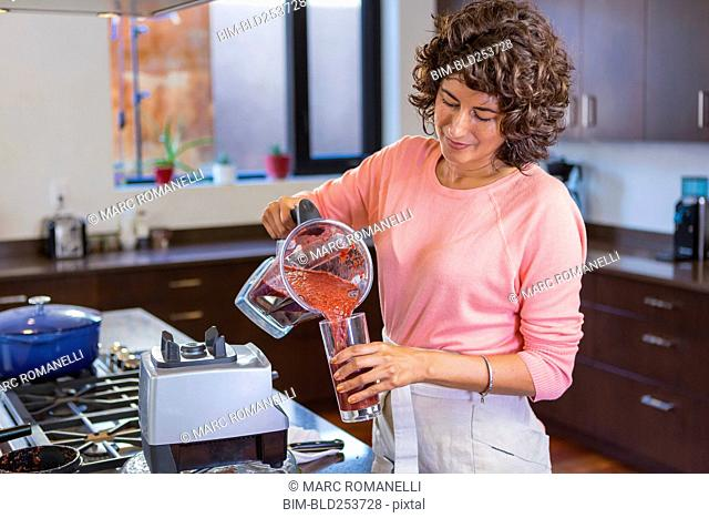 Hispanic woman pouring smoothie from blender into glassware