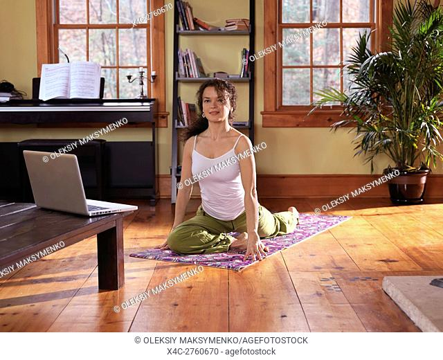 Woman practicing yoga at home in a living room on bright sunny day