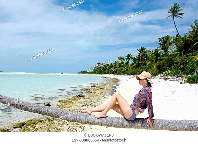 Young, sexy woman relaxing on coconut palm tree on a deserted tropical island in Aitutaki Lagoon, Cook Islands