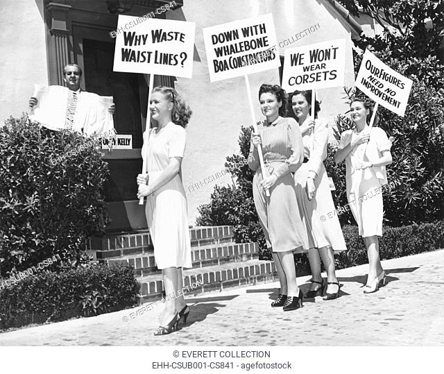 The Lane Sisters with Gail Page protest famous Hollywood costume designer, Orry-Kelly. Aug. 28, 1939. The Warner Brothers, designer Orry Kelly holds a corset