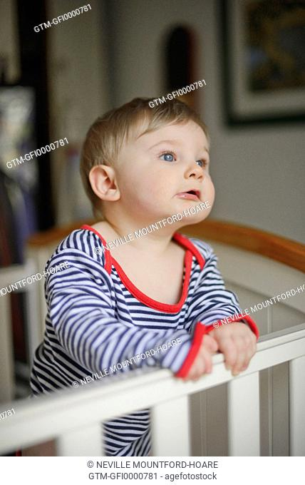 Baby standing in cot with intense look