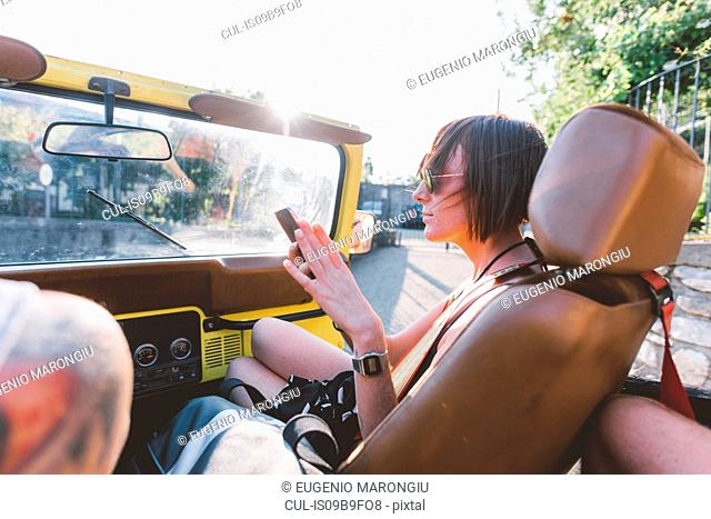 Young woman looking at smartphone in off road vehicle, Como, Lombardy, Italy