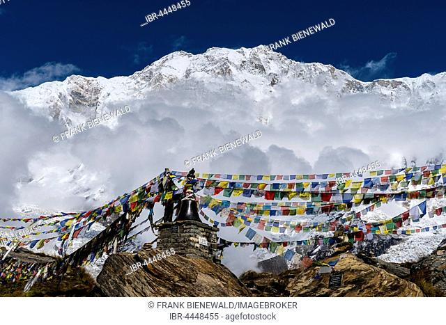 Many tibetan prayer flags are set up at a memorial for died climbers, back snow covered Annapurna 1 North Face, partly covered by monsoon clouds, Chomrong