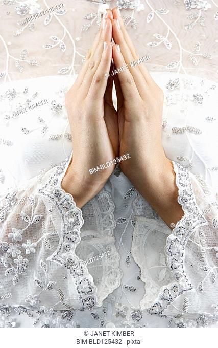 Mixed race bride's hands in prayer position