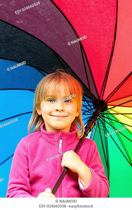 Portrain of little girl wearing pink fleece jacket holding colorful umbrella