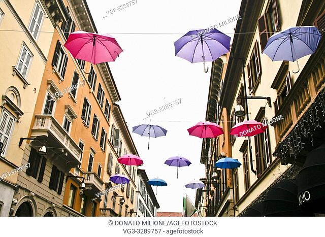 Monza, Brianza, Lombardy, Northern Italy. A downtown street with an artistic installation with open rain umbrellas suspended in the air