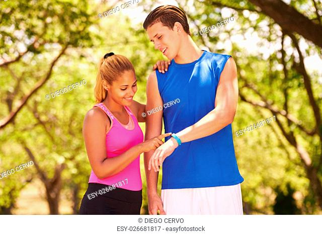 Young people doing sport activities, girl and friend running, man and woman using fit watch. Concept of eisure, health, recreation, fitness, exercising