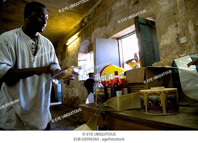 Male worker hand labelling the bottles at the River Antoine rum distillery
