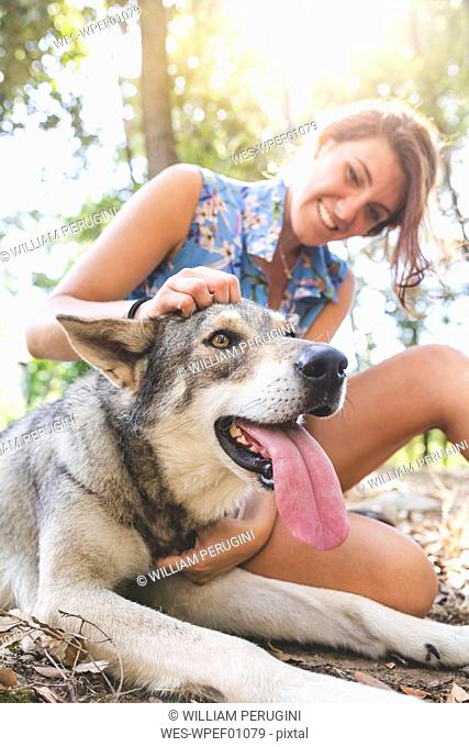 Smiling young woman sitting on forest floor stroking her dog