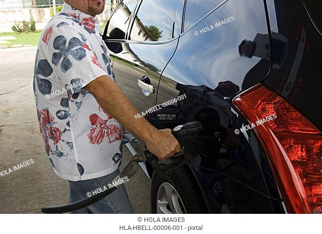 Man putting gasoline into car