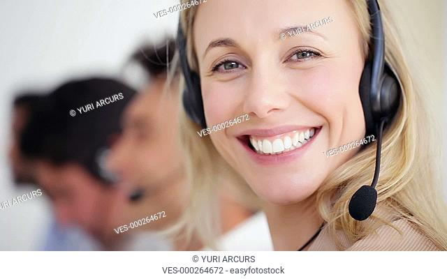 Closeup footage of a young call centre assistant smiling at the camera with her colleagues blurred in th background