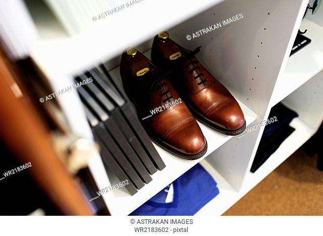 High angle view of brown shoes and books in shelf