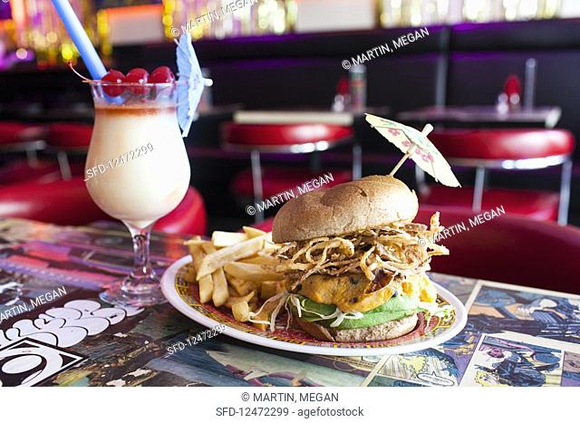 Vegan burger with avocado, soy cheese, fried onions, french fries and coconut and scotch cocktail