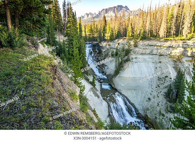 Long exposure of water cascading down Brooks Lake Creek Falls with mountains peaking out above the forest, Dubois, Wyoming. USA