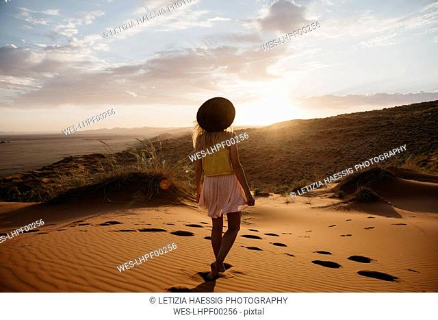 Namibia, Namib desert, Namib-Naukluft National Park, Sossusvlei, woman walking on Elim Dune at sunset