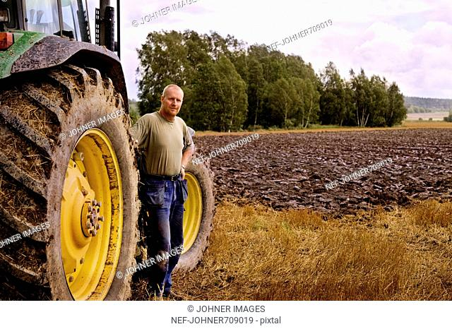A farmer and a tractor on a field, Sweden