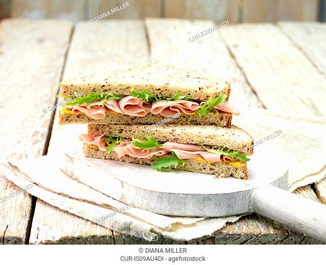 Wafer thin ham, mustard and salad leaf sandwich on sliced seeded bread