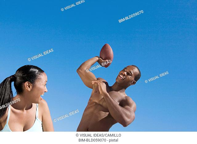 Multi-ethnic couple playing football