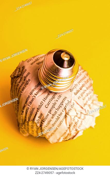 Turning a news story upside down a newspaper lightbulb illuminates fictional press ideas on yellow background