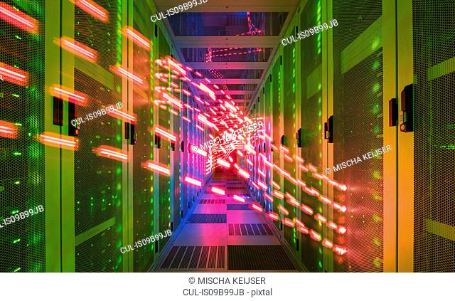 Interior of data centre, lights trails showing travelling data