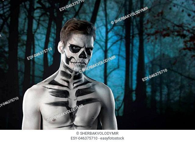 halloween scary skeleton man portrait in studio at dark forest