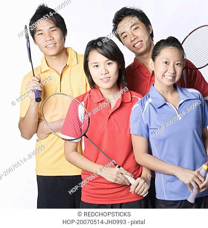 Portrait of two young couples holding badminton rackets and smiling