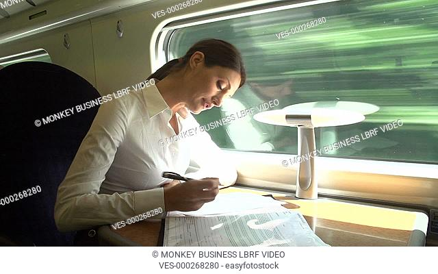 Businesswoman sitting at table on train working on document.Shot on Sony FS700 in PAL format at a frame rate of 25fps