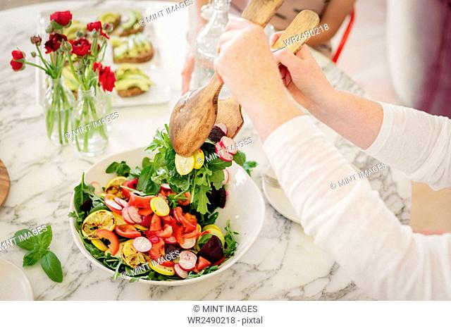 View from above of a table laid with cutlery and plates of prepared food. A woman taking a serving of salad