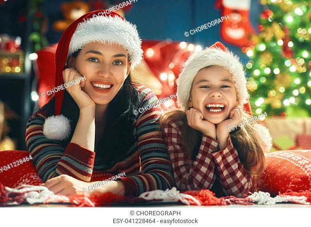 Merry Christmas and Happy Holiday! Mom and daughter near the tree at home