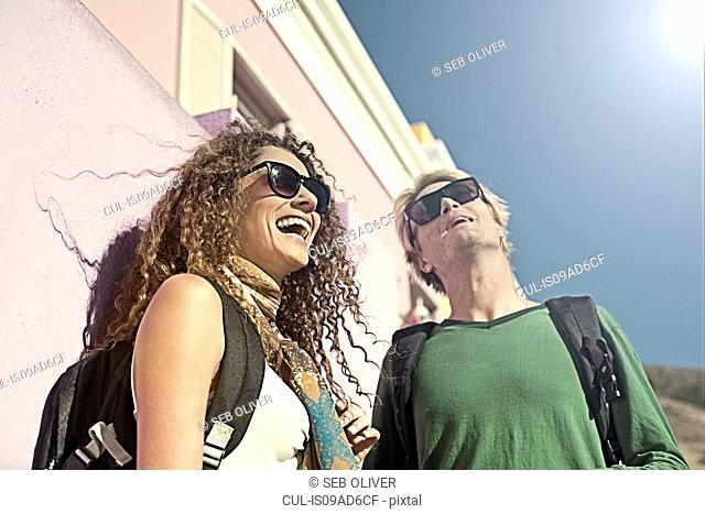 Young couple standing outside of painted house, looking up and laughing