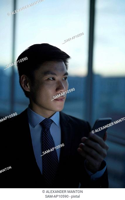 Singapore, Businessman standing by window, using smartphone