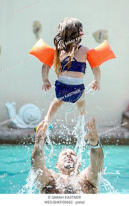 Father playing with little daughter in swimming pool