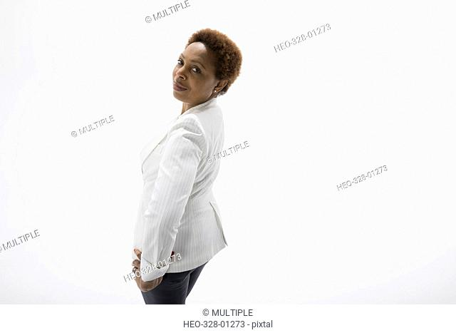 Portrait confident businesswoman with hands on hips against white background