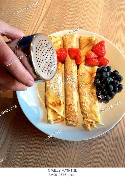 Homemade Bavarian pancakes with strawberries, sugar powder and fresh blueberries