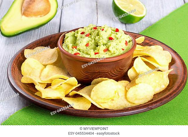 bowl of guacamole dip and potato chips on a clay brown dish, on a green table mat with slice of lime on a white wooden background, close-up