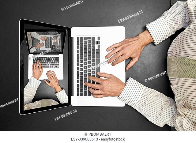 Businessman wearing a white shirt and green tie working on his laptop. Droste effect on screen